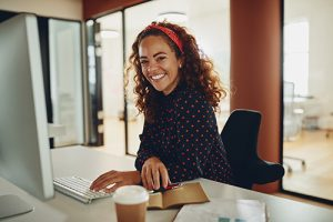 Smiling young businesswoman working on her office computer