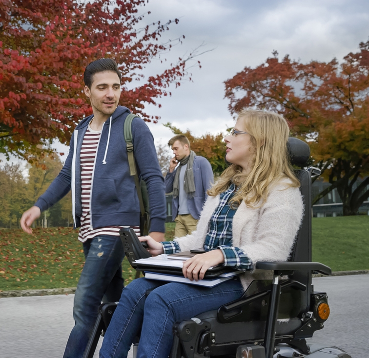 Male student talking with female student sitting on powered wheelchair at university campus